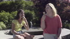 Girls Eat Ice Cream Cones And Chat, Sit On Edge Of Fountain In Park (4K) Stock Footage