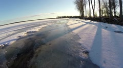 Low height aerial along frozen river bank in a sunny winter day Stock Footage