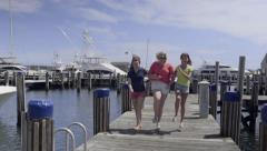Carefree Teenage Girls Skip Down A Dock In A Marina (Slow Motion) - stock footage