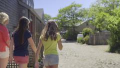 Girls Walk Down Cobblestone Street Together In Quaint Town Of Nantucket Stock Footage