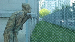 Groveling sculpture behind chain link fence Stock Footage