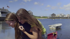 Girl Gives Friend Piggyback Ride Up Beach In Quaint New England Town Stock Footage
