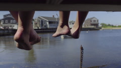 Teen Girls Sit On A Dock And Swing Their Bare Feet Back And Forth (Slow Motion) Stock Footage