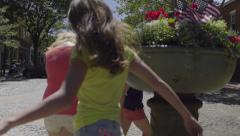 Teens Skip Around Ornamental Flower Pot In A Quaint New England Town Rotary Stock Footage
