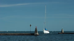 Sailboat navigating breakwater on clear day Stock Footage