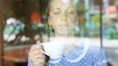 Woman  drinks coffee and looking out the window at the coffee shop - stock footage