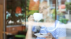 The girl is drinking coffee and looking out the window at the coffee shop - stock footage