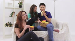 Three young people have a party and eating different fruits Stock Footage