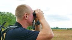 Man tourist looks in binocular in  outdoor place. 4K 3840x2160 Stock Footage
