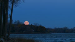 Orange moon rise over the water - stock footage