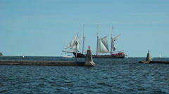 tall ship passes beyond breakwater - stock footage