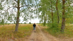 Man tourist  walking with stocks on rural road. 4K 3840x2160 Stock Footage
