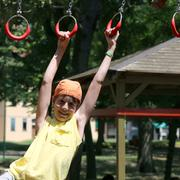child plays with rings of outdoor playground - stock photo