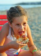 Beautiful Little Girl eats a slice of pizza on the beach at sunset in summer Stock Photos