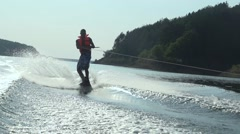 Boy slide on the water surface in water skiing in slow motion in a  lake - stock footage