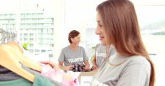 Smiling young female volunteer separating clothes Stock Footage