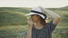 Woman With Hat Smelling a Flower Stock Footage