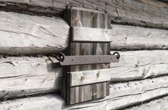 Closed wooden shutter on aged wall of log cabin - stock photo