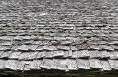 Old and weathered wooden roof shingle, blurred texture and background Stock Photos