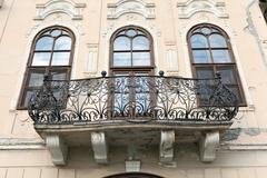Balcony on a castle with three windows and the wrought iron bani Stock Photos
