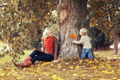 Family in autumn park! Happy mother and child having fun together Stock Photos