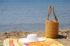Hat Bag and Towel on the Beach Stock Photos