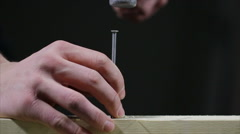 Man punching a nail through wood while dust rises Stock Footage