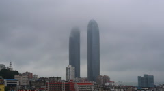 time lapse: foggy and clouds moving around skyscapers - stock footage