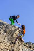 Climber helps her partner to rich the summit Stock Photos