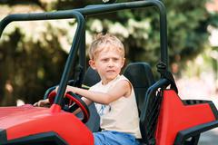 Boy drive electric mini park in park Stock Photos