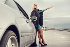 Lady in high heel shoes with broked car on the highway Stock Photos