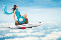 Young woman sitting on airplane - stock photo