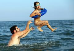 Daddy plays with her daughter by making her do high dives in seawater - stock photo