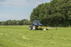 Pasture mowing with blue tractor Stock Photos