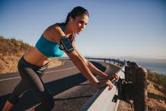 Young female athlete leaning on guardrail - stock photo