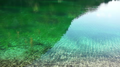 Reflections of trees and mountain at lake Bluntausee in austria - stock footage