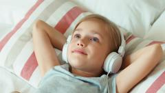 Closeup portrait girl child listening music in headphones and resting lying Stock Footage