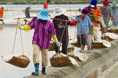 People carry salt at the salt farm in Huahin, Thailand - stock photo