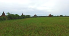 4k aerial low flight from grass field to crane shot of Thatbyinyu temple Stock Footage