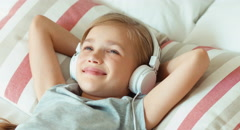 Closeup portrait girl listening music in headphones with eyes closed and lying Stock Footage