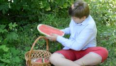 Teen boy eating watermelon in nature Stock Footage