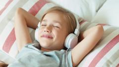 Closeup portrait girl child listening music in headphones with eyes closed Stock Footage
