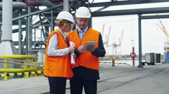 Business People in Safety Vests Using Tablet in Industrial Environment Stock Footage
