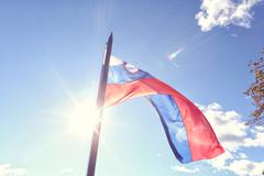 Slovenian flag in the wind - stock photo