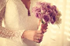 Bride holding wedding bouquet made of roses - stock photo