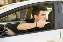 Young Man Driving a Car and showing the middle finger - stock photo