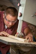 Professional carpenter working with sawing machine. - stock photo