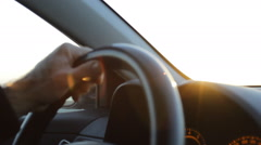 Close Up of hands on the steering wheel while driving on sunset Stock Footage