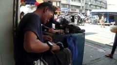 Shoe repair job at street sidewalk Stock Footage