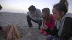 Friends light fire at the beach Stock Footage